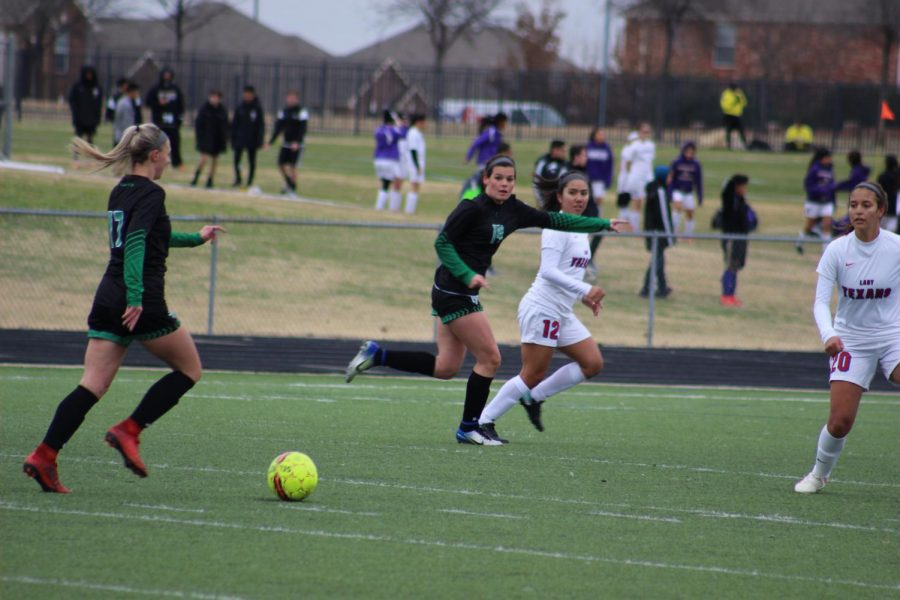 Journie Long and Kara Moore taking the ball to the goal.