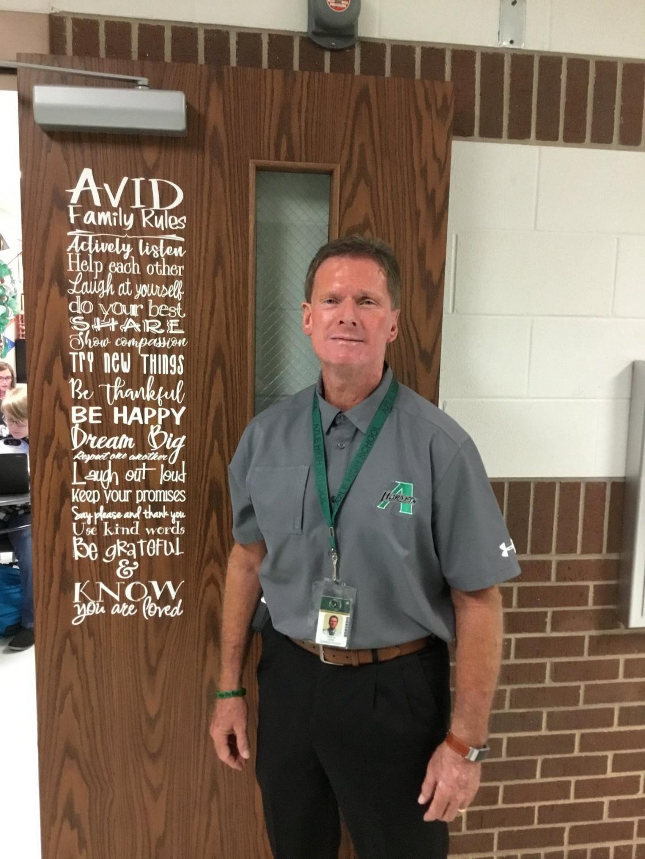 Principal Randy Cobb showing off AVID instructor Keri Dorris' new door art.
