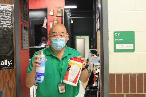 Mr. G shows off his cleaning supplies outside his classroom.