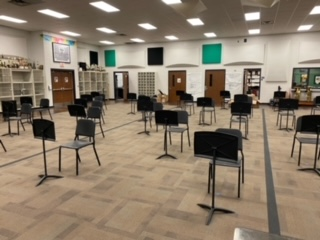 Chairs in the band hall placed 6 feet apart for students.