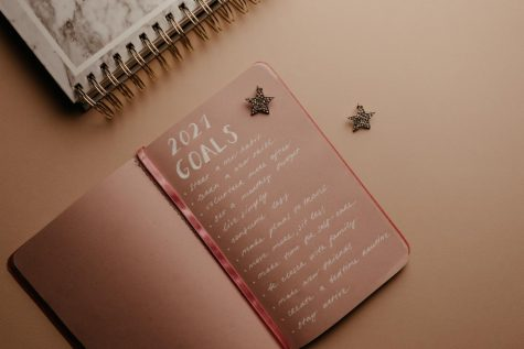 A notebook is shown with goals for 2021 written.