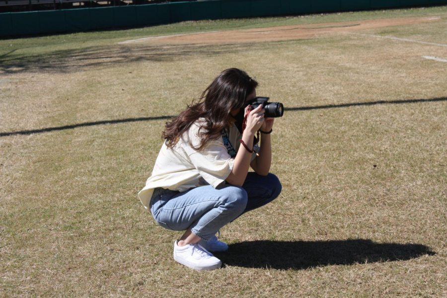Senior Bailee Johnson taking a photo of the baseball field
