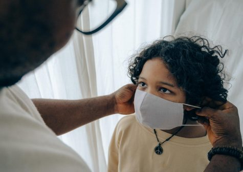 An adult is seen putting a mask on a child.