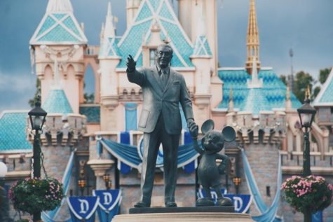 A statue of Walt Disney and Mickey Mouse is shown in front of the Cinderella Castle at Disneyland.