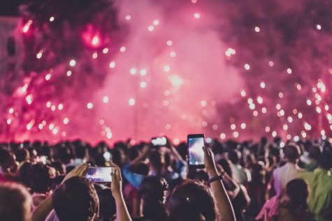 A music festival is seen with a large crowd. https://www.pexels.com/photo/people-taking-photo-of-the-fireworks-3052448/